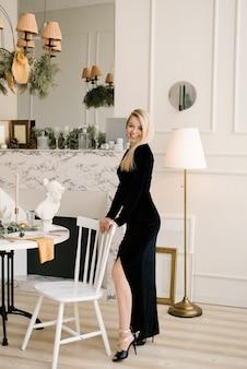 Weihnachtsporträt einer lächelnden blonden frau in einem schwarzen kleid