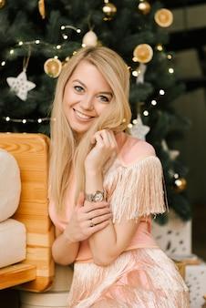 Weihnachtsporträt einer lächelnden frau in einem rosa kleid