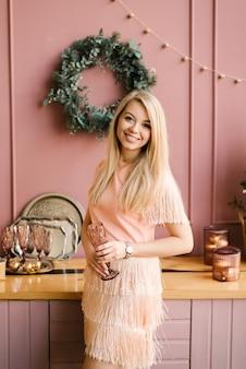 Weihnachtsporträt eines mädchens in einem rosa kleid und einem schaffellmantel