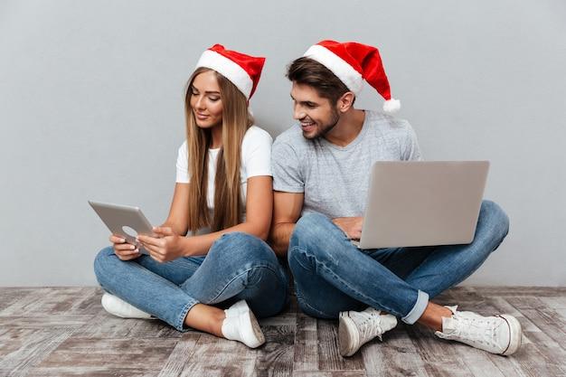 Weihnachtsporträt eines paares mit laptops