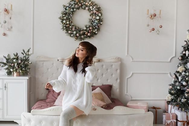 Weihnachtsporträt eines schönen modellmädchens im strickkleid in dekoriert für neujahrsausstattung.
