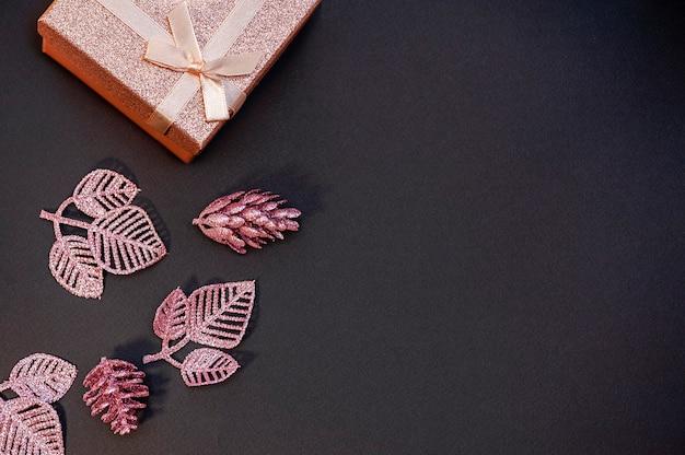 Weihnachtsrahmen aus glänzender geschenkbox und dekorationen auf schwarzem hintergrund