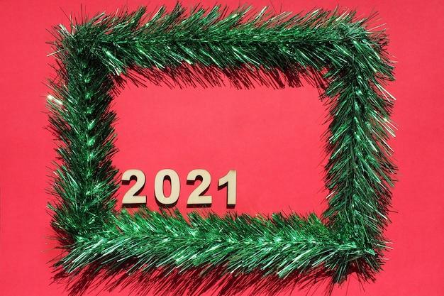 Weihnachtsrahmen aus grünem lametta auf rot