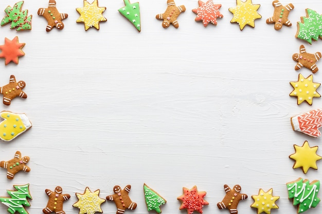 Weihnachtsrahmen aus lebkuchenplätzchen mit zuckerguss auf weißem holzhintergrund