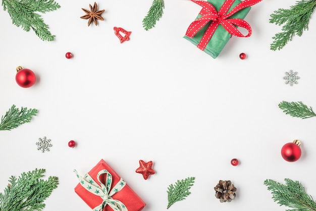 Weihnachtsrahmen aus tannenbaum geschenkbox rote dekorationen auf weißem hintergrund