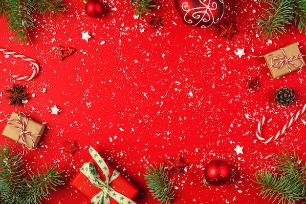 Weihnachtsrahmen aus tannenzweigen, geschenkboxen, roten feiertagsdekorationen und süßigkeiten auf rotem hintergrund mit schnee. weihnachten oder guten rutsch ins neue jahr-konzept. flach liegen. draufsicht mit kopienraum