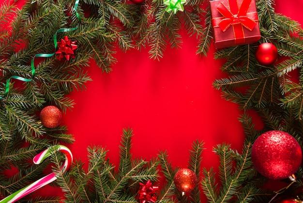 Weihnachtsrahmen aus tannenzweigen, geschenkboxen, roten weihnachtsdekorationen und süßigkeiten