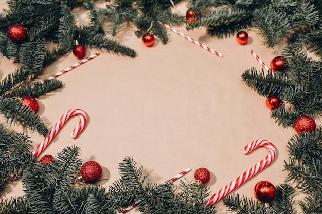Weihnachtsrahmen aus tannenzweigen, roten kugeln, lakritzstangen, girlanden