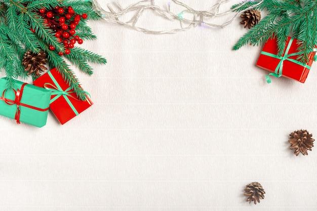 Weihnachtsrahmen aus tannenzweigen, roten stechpalmenbeeren, weihnachtsgeschenken, weihnachtstapete. flache lage, draufsicht, kopierraum.