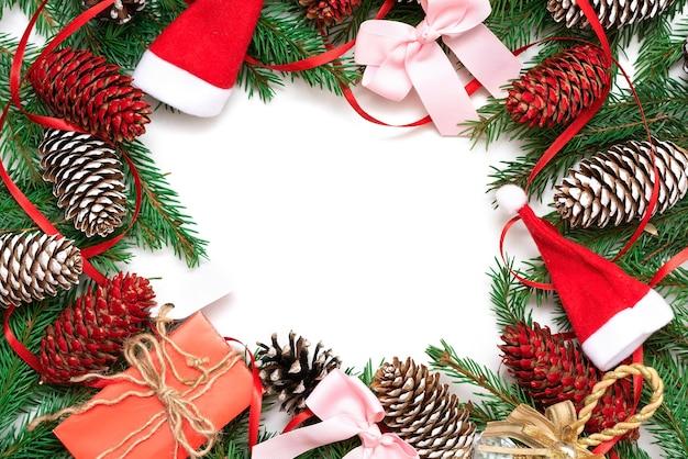 Weihnachtsrahmen aus tannenzweigen und zapfen auf weißem grund mit bändern.