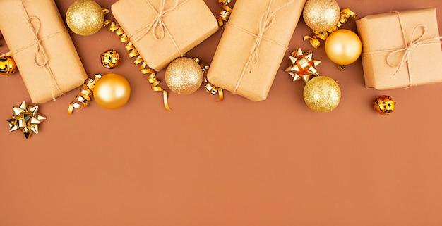 Weihnachtsrahmen aus weihnachtsgoldkugeln und geschenkboxen auf braunem hintergrund. speicherplatz kopieren.