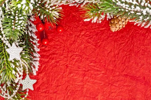 Weihnachtsrahmen aus zweig und dekorationen auf altem papierhintergrund