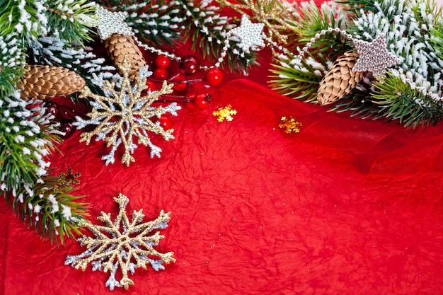 Weihnachtsrahmen aus zweig und dekorationen auf rotem papierhintergrund