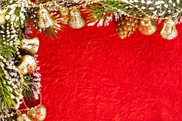 Weihnachtsrahmen aus zweig und glocken auf rotem papierhintergrund