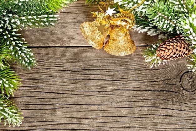 Weihnachtsrahmen aus zweigen und dekorationen auf altem holzhintergrund