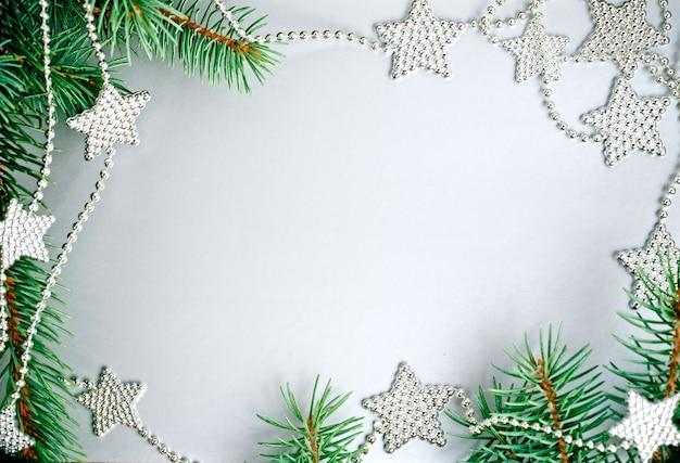 Weihnachtsrahmen aus zweigen und dekorationen auf silbernem hintergrund