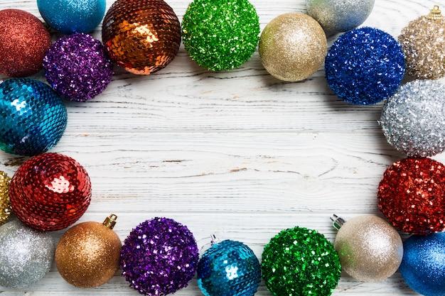 Weihnachtsrahmen gemacht von den dekorativen bällen auf hölzernem hintergrund