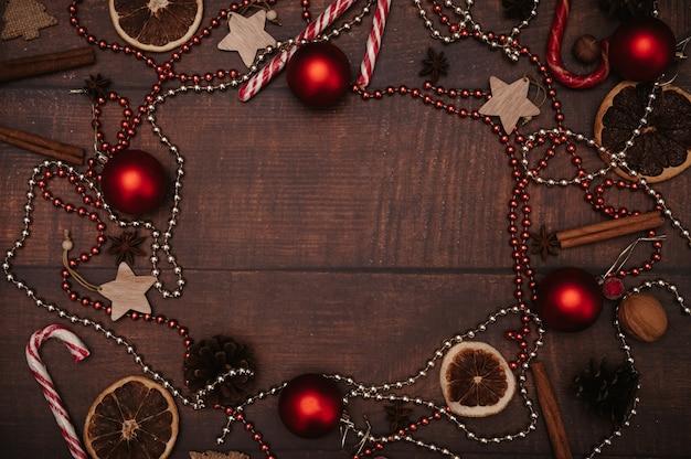 Weihnachtsrahmen im flatley-stil mit weihnachtsschmuck aus kugeln, zapfen, gewürzen. das konzept, das neue jahr zu feiern. ansicht von oben.