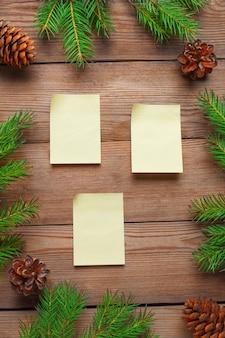Weihnachtsrahmen mit aufklebern für anmerkungen, mit fichtenzweigen und kegeln auf einem natürlichen hölzernen.
