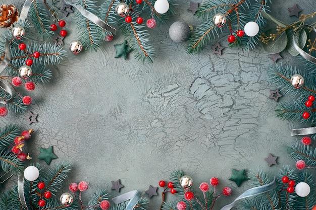Weihnachtsrahmen mit den tannenzweigen, den schmuckstücken in rotem und in grünem, den sternen, den bällen, den beeren und den bändern