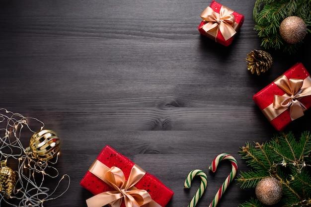 Weihnachtsrahmen mit kiefer, geschenken, goldenen kugeln auf dunklem holz