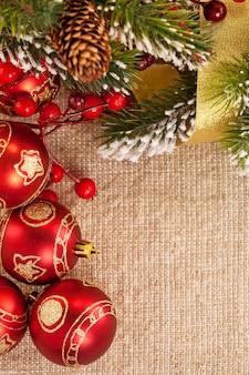 Weihnachtsrahmen mit niederlassung und dekorationen auf sackleinenhintergrund