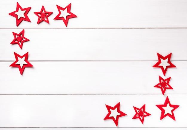 Weihnachtsrahmen mit roten sternen auf weißem holz