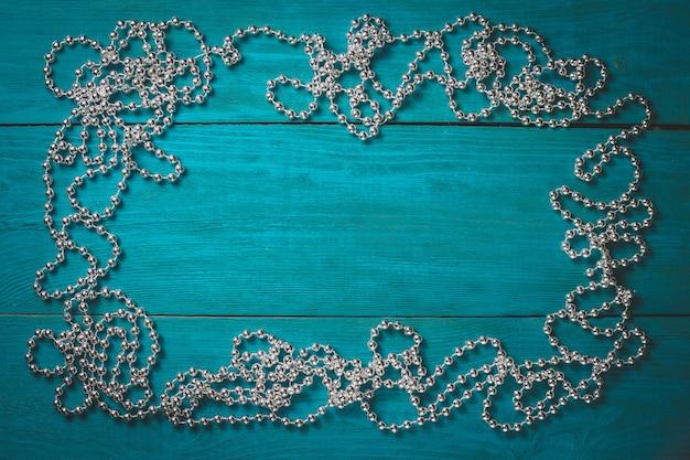 Weihnachtsrahmen mit silbernen perlen auf einem blauen hölzernen hintergrund
