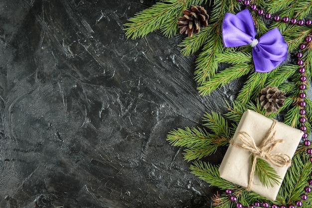 Weihnachtsrahmen mit tannenzweigen, geschenkbox und tannenzapfen auf schwarz.