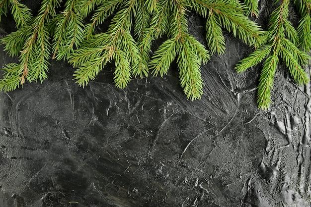 Weihnachtsrahmen mit tannenzweigen, geschenkbox und tannenzapfen auf schwarzer oberfläche.