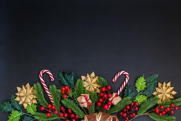 Weihnachtsrahmen mit tannenzweigen, süßigkeit, geschenken und goldsternen auf dunkelheit