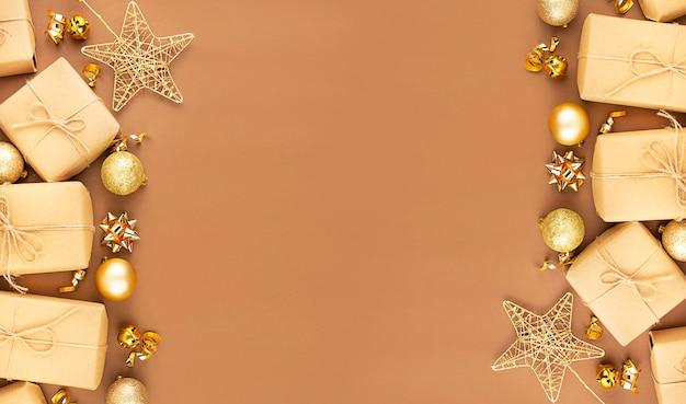 Weihnachtsrahmen von den goldenen weihnachtskugeln und von geschenkboxen auf einem braunen hintergrund. kopie des raumes.