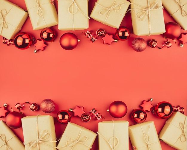 Weihnachtsrahmen von geschenkboxen, roten kugeln, serpentin auf einem roten hintergrund. weihnachtshintergrund.
