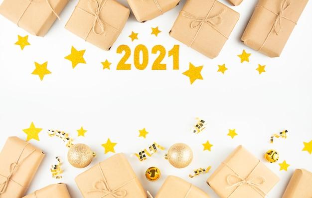 Weihnachtsrahmen von geschenken und neujahrsspielzeug, eine goldene inschrift 2021 auf einem hellen hintergrund.