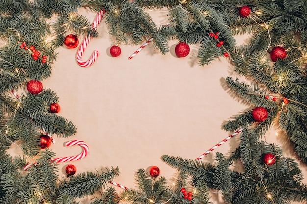 Weihnachtsrahmen von tannenzweigen, roten kugeln, lakritzstangen, girlandenhintergrund