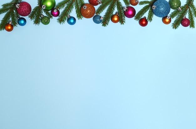 Weihnachtsrahmen von tannenzweigen und farbigen kugeln auf blauem hintergrund