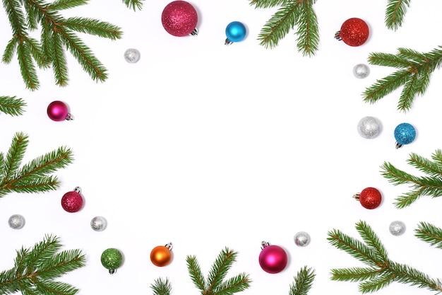 Weihnachtsrahmen von tannenzweigen und farbigen kugeln auf weißem hintergrund