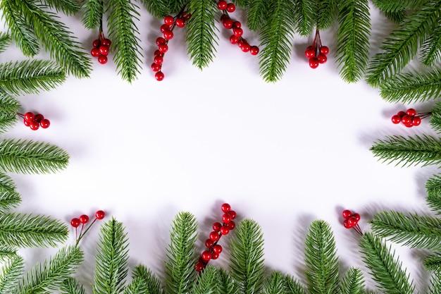 Weihnachtsrahmenhintergrund mit tannenzweigen und stechpalmenbeeren. kopieren sie platz.