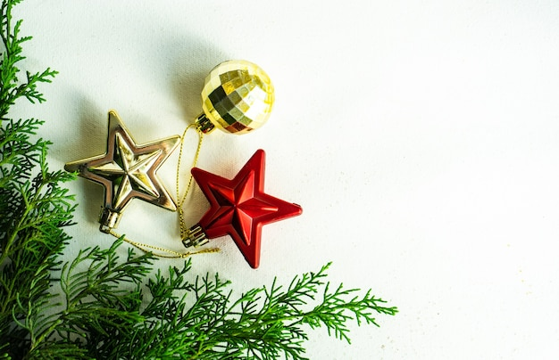 Weihnachtsrahmenkonzept mit immergrüner thuja-pflanze und sternförmigen kugeln