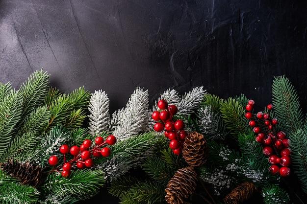 Weihnachtsrahmenkonzept mit weihnachtsbaumzweigen und rotem feiertagsdekor auf grauer steinoberfläche mit kopienraum