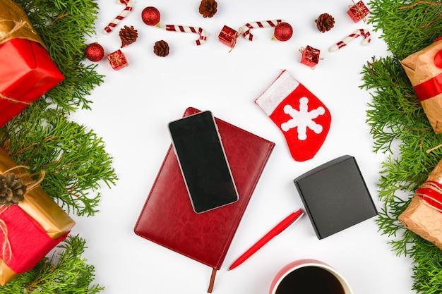 Weihnachtsraum von notizblock, telefon, kaffeetasse. keramische rote tasse mit schwarzem kaffee. neujahrslayout. sicht von oben. eine weibliche hand schreibt in ein notizbuch mit adern.