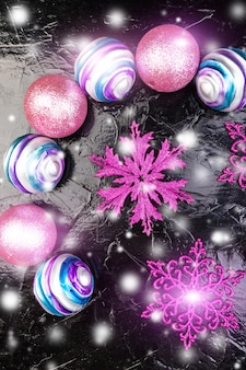 Weihnachtsrosa und purpurrote bälle und dekorative schneeflocken. flach liegen.