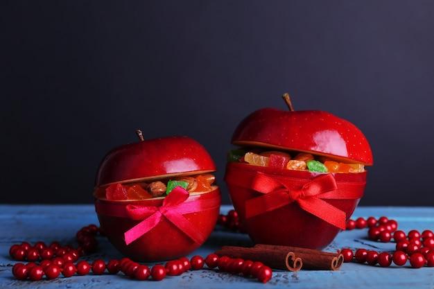 Weihnachtsrote äpfel gefüllt mit getrockneten früchten auf farbigem holztisch und dunklem hintergrund