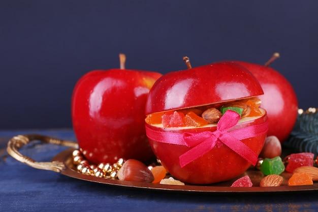 Weihnachtsrote äpfel gefüllt mit getrockneten früchten auf metalltablett auf farbigem holztisch und dunklem hintergrund