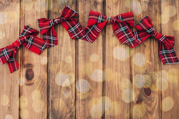 Weihnachtsrote bögen auf braunem holzhintergrund mit lichtern bokeh
