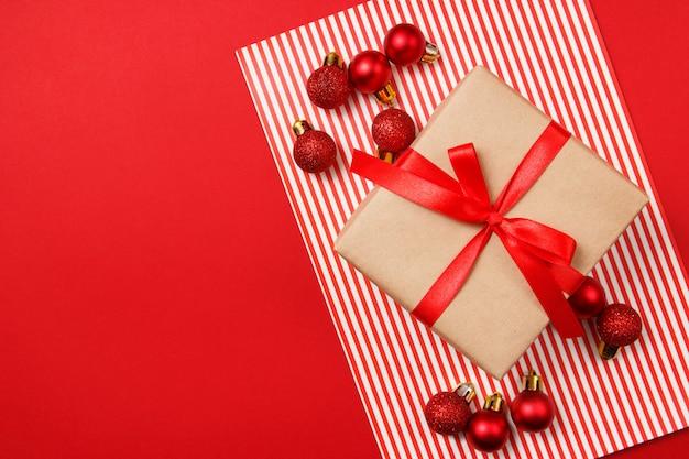 Weihnachtsrote funkelnbälle und kraftpapiergeschenk auf rotem hintergrund.