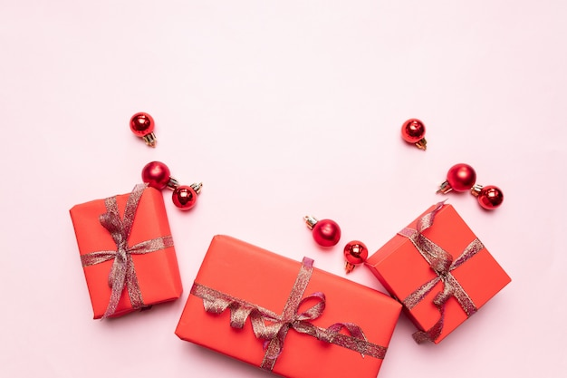 Weihnachtsrote geschenkboxen, bälle auf pastellrosa. feiertagsgrußkarte der festlichen feier mit copyspace