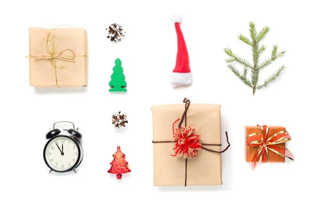 Weihnachtsrote weihnachtsmütze, weinleseuhr, feuerbaumzweig, dekorationen und geschenke auf weiß