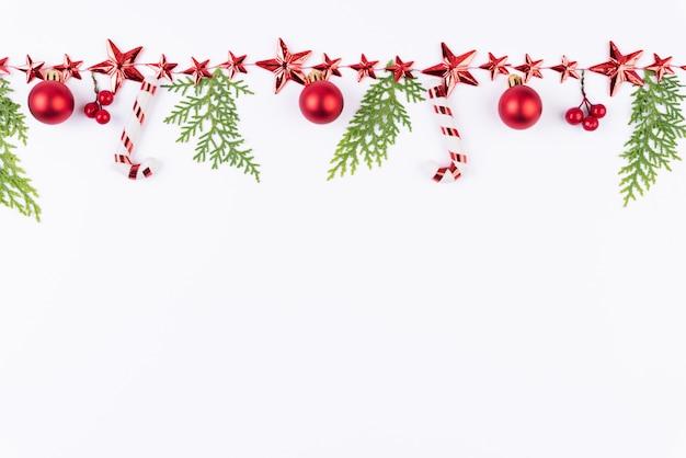 Weihnachtsroter ball mit grünen fichtenzweigen und stern auf weißem hintergrund.