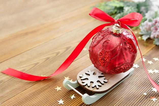 Weihnachtsroter flitter auf pferdeschlitten mit rotem bandbogen, auf hölzerner rustikaler tabelle